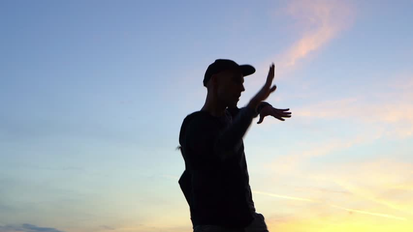 Stilish young man dancing outdoor at sunset | Shutterstock HD Video #1018068595