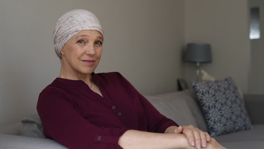Mature woman with cancer in pink headscarf smiling sitting on couch at home and looking away. Mid woman suffering from cancer sitting after taking chemotherapy sessions looking at camera. | Shutterstock HD Video #1018068925