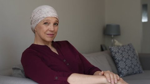 Mature woman with cancer in pink headscarf smiling sitting on couch at home and looking away. Mid woman suffering from cancer sitting after taking chemotherapy sessions looking at camera.