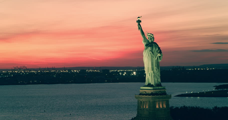 Aerial view of the Statue of Liberty orbiting   at sunset, New York City, during summer. Wide shot. 4k shot with a RED camera.