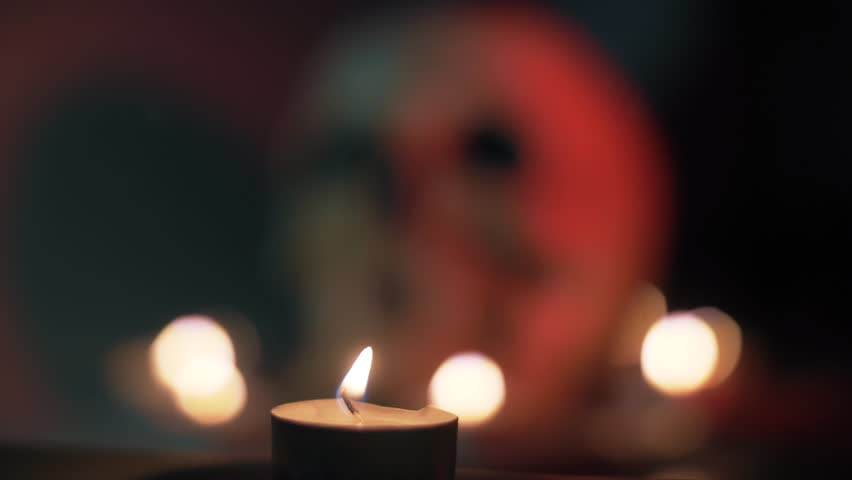 Flame of a burning candle against the background of a blurred skull, Halloween theme.    Shutterstock HD Video #1018155925
