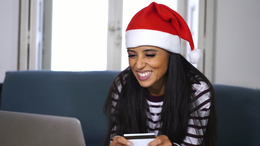 Woman wearing red sweater and santa claus hat choosing and buying christmas gifts online using a laptop sitting on a couch in the living room at home excited about having all ready for christmas. | Shutterstock HD Video #1018159465