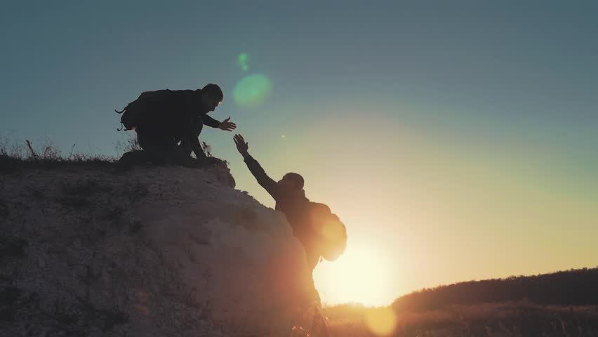 Silhouette of helping hand between two climber. two hikers on top of the mountain, a man helps a man to climb a sheer stone. couple hiking help each other silhouette in mountains with sunlight. #1018162975