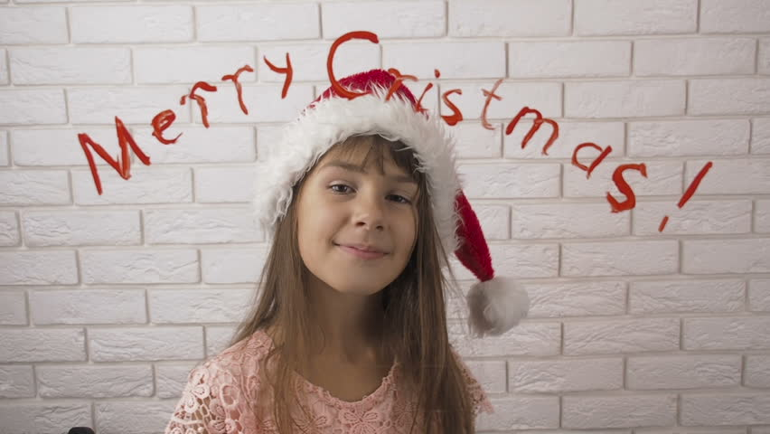 Merry Christmas. A child in a Santa Claus hat. The inscription on the glass. | Shutterstock HD Video #1018176685