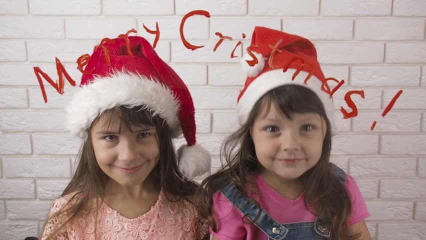 Merry Christmas. Children in Santa Claus hat. Sisters dancing in Santa's hats. | Shutterstock HD Video #1018177465