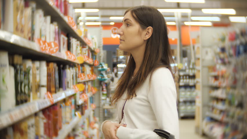 Beautiful woman choosing body care products in supermarket. | Shutterstock HD Video #1018179325