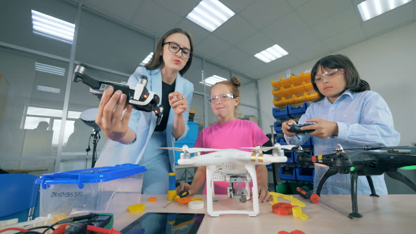 Technology teacher is instructing children on how to control a quadcopter, drone.   Shutterstock HD Video #1018188235