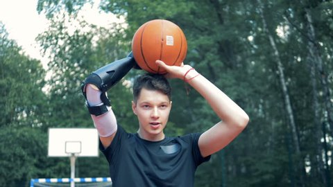 Teenage boy with a prosthetic hand is throwing a basket-ball.