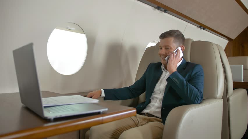 Rich entrepreneur talking by mobile phone partner connection aircraft jet travel. He have positive conversation with happiness and good mood by mobile and work on laptop. 4K UHD | Shutterstock HD Video #1018189795