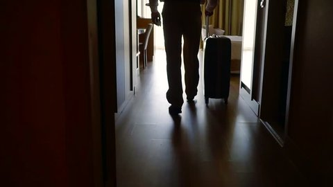 businessman is walking in hotel room, holding suitcase with wheels, back view