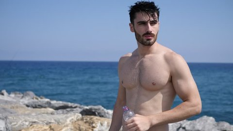 Attractive shirtless muscleman on the beach drinking water from plastic bottle
