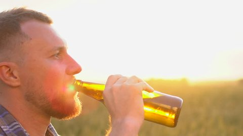 people, drinks and alcohol concept - close up of bearded young man drinking beer from bottle at hot summer day on a wheat field at sunset background outdoors. guy Sun lens flare. slow-motion, close-up