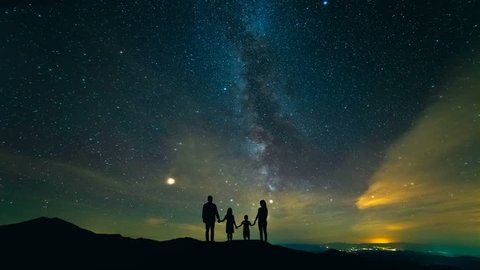 The family standing on the mountain against the starry sky. night time