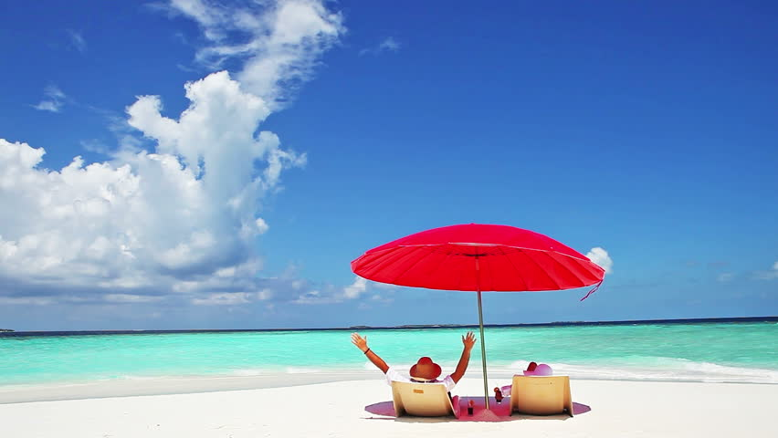 Happy, mid age couple resting on deckchairs under a red parasol at white sand beach in Maldives island