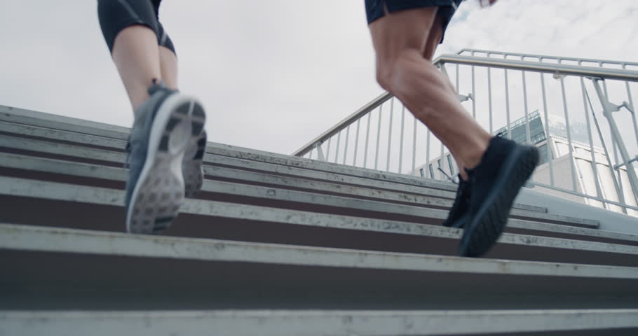 Two athletic runners legs running up stairs friends training together in urban city doing intense cardio exercise close up | Shutterstock HD Video #1018214575
