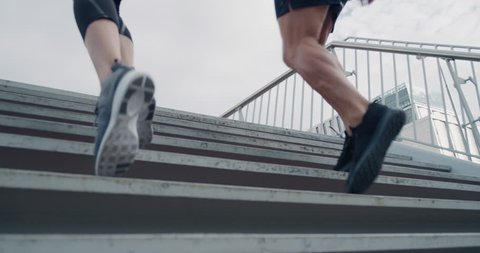 two athletic runners legs running up stairs friends training together in urban city doing intense cardio exercise close up