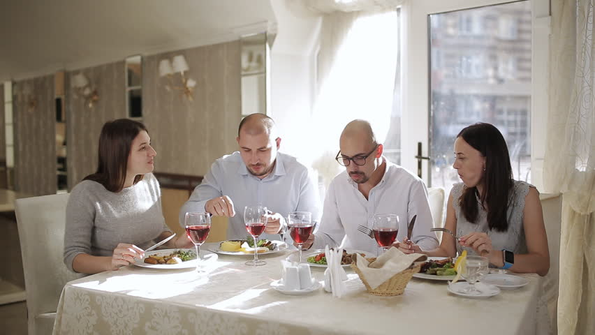 Concept - happy friends eating and drinking at restaurant.Four friends in the restaurant, eat meat and drink red wine in the glass. | Shutterstock HD Video #1018234135