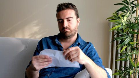Video is about one man reading a bad news letter pink slip at home