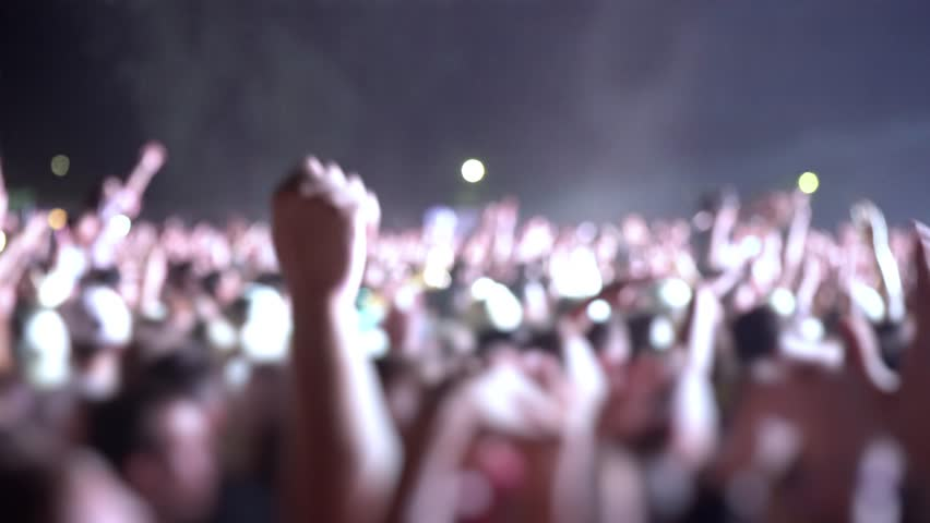 Happy people are watching an amazing musical concert. Merry fans jump and raise their hands up. Crowd of excited fans applauding to popular band performing favorite song. A group of fans with phones | Shutterstock HD Video #1018316905