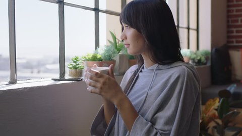 beautiful young asian woman drinking coffee at home enjoying relaxed morning looking out window planning ahead thinking contemplative female in trendy apartment