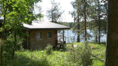 Sunny view of a lakeside log cabin in skandinavia