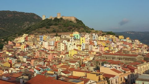 Video from above, aerial view of the beautiful village of Bosa with colored houses and a medieval castle. Bosa is located in the north-wesh of Sardinia, Italy.