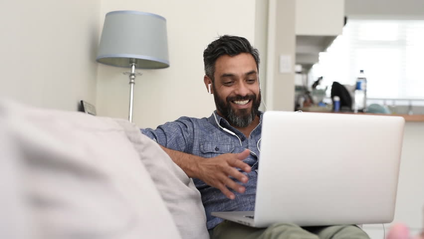 Relaxed mature man using laptop with earphones for a video call. Cheerful  smiling latin man sitting on couch having a friendly video call.