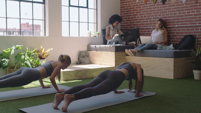 Young business women practice yoga meditation together in office doing cobra pose enjoying mindfulness exercise relaxing on lunch break | Shutterstock HD Video #1018432675