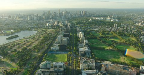 Aerial sunset view with sun flare St Kilda Road through Albert Park to Melbourne city skyline Victoria Australia