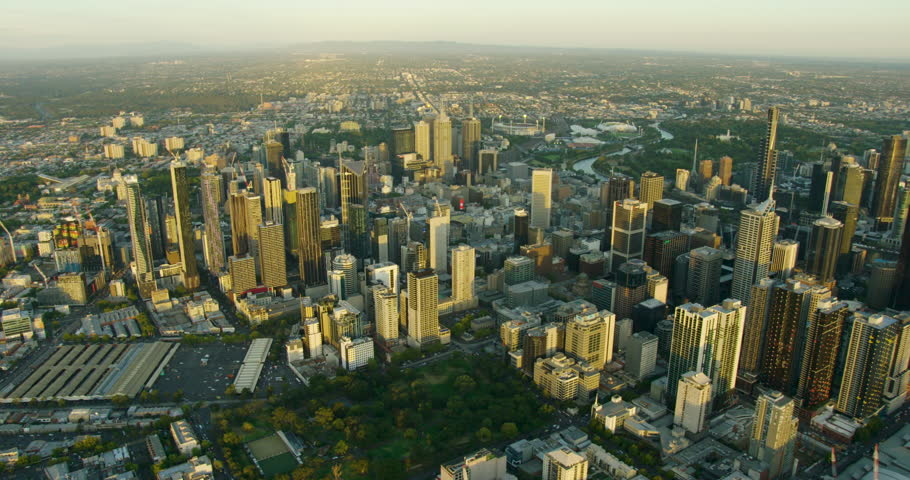 Aerial view over Melbourne CBD skyscrapers at sunset with Queen Victoria Market and Carlton Gardens Victoria Australia #1018440025