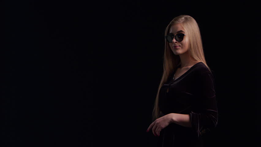 Woman in cool sunglasses and black dress, holding black shopping bag isolated on dark background in black friday holiday or christmas | Shutterstock HD Video #1018514245
