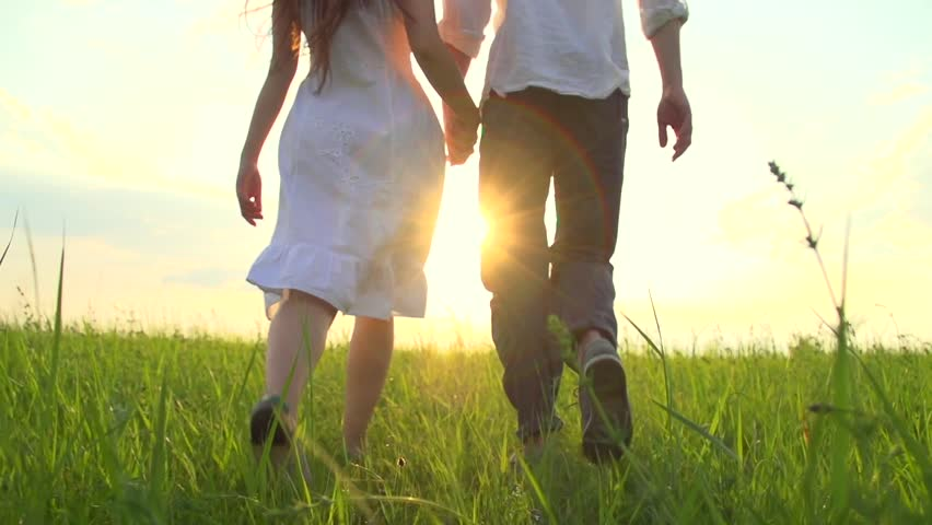 Happy Young Couple Walking on Summer field and smiling, holding hands walk through a wide field, having fun outdoors. Countryside. Man and woman on the meadow. Sun flare. Slow motion Full HD 1080p | Shutterstock HD Video #10185455