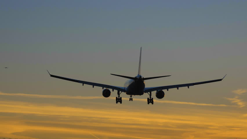 Silhouette of Airplane Landing at the Airport at Colorful Sunset. Slow Motion. Rear View   Shutterstock HD Video #1018558015