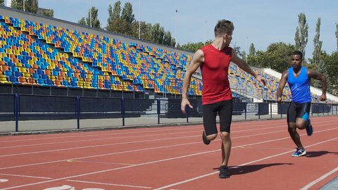 Athletes training relay race on empty stadium, teamwork, aspiration to win