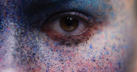 close up macro woman eye wearing face paint body art mysterious female performer with colorful makeup light fading to dark