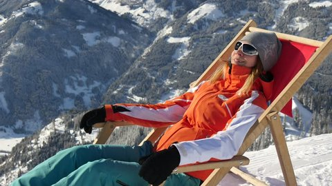 Woman lying in sunbed on top of the mountainvat ski resort in winter
