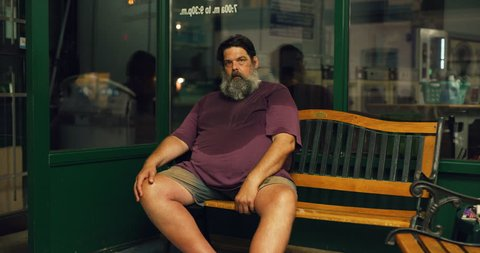 Portrait of sweaty bearded man sitting on bench in interior small laundromat with bright interior lighting. Wide to Medium shot on 4k RED camera.