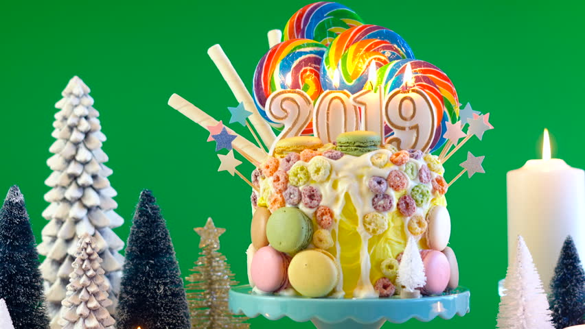 on white background happy new years candy land lollipop drip cake with 2019 candles on greenscreen background