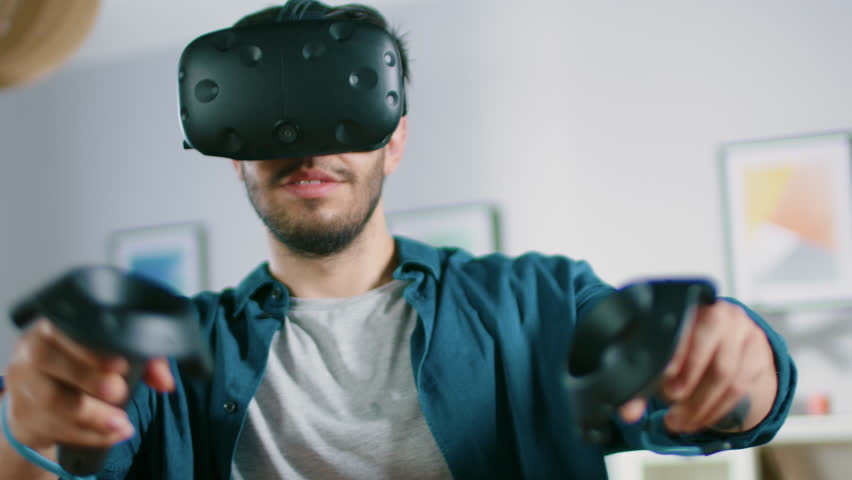 faf355e33cdc Energetic Young Man Wearing Virtual Reality Headset and Holding Controllers  Plays in a Video Game at Home. Active Man Playing VR Quest Adventure  Videogame ...