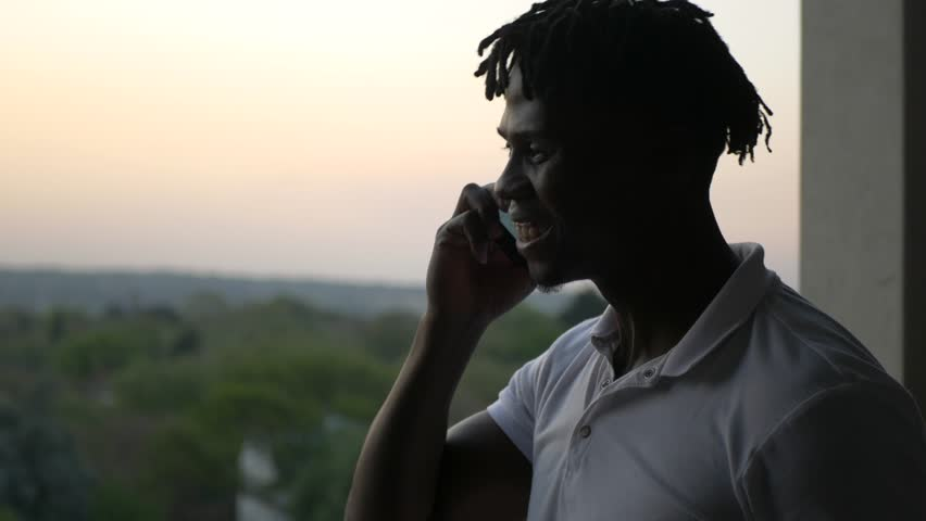 A South African happy black man moving around and talking on a telephone cellular cell phone during sunset. #1018667935