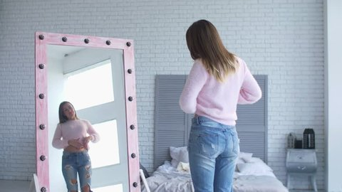 Beautiful adult woman in loose panrs admiring her body shape and appearance after losing weight while standing in front of big mirror in domestic room. Happy female showing weight loss success.