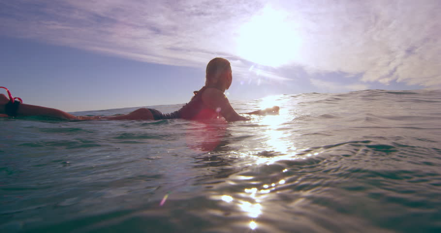 Professional female surfer swimming over an ocean wave on surfboard in Australian beach with bright day lighting. Wide shot on 4k RED camera. | Shutterstock HD Video #1018684015