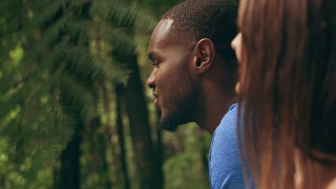 Interracial couple talking and laughing in an Australian rainforest through shaded green dense treebed during daytime. Closeup shot on 4k RED camera.