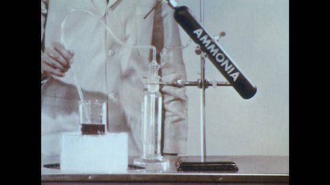 1960s: Lab. Man removes tubing from beaker and stops flow of ammonia. Man compares liquid in beaker to tray of test tubes. Man puts down beaker.