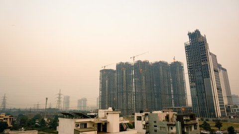 evening dusk to night timelapse of under construction building in gurgaon, delhi, mumbai, hyderabad, bangalore india. Shows lights being switched on, crane, construction, lift, busy streets and
