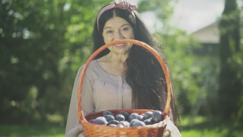 Old smiling woman holding a basket with plums | Shutterstock HD Video #1018796485