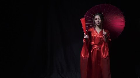Japanese woman in national clothes unfolds the fan in slow motion while holding an umbrella
