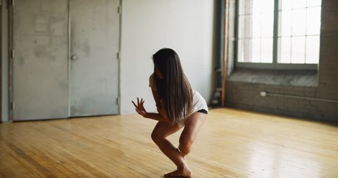 Dainty asian dancer pirouettes in industrial wood and brick windowed loft during daytime. Wide to long shot on 4K RED camera.