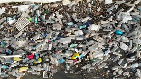 Spain - October 28, 2018: Aerial drone video waterfront heap pile of garbage. Above top view plastic bottles rubbish pollution marine debris on lake shore. Global damage environmental dumping concept