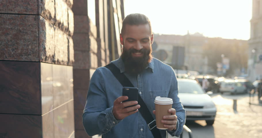 Attractive Caucasian young hipster man with a beard chatting on the smartphone cheerfully and smiling while stepping the town with a coffee in a hand. Outdoors. #1018905025